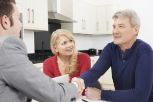 Mature Couple Shaking Hands With Wills Advisor At Home